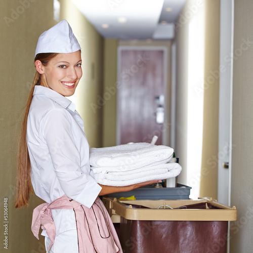 Zimmermädchen im Hotel mit Reinigungswagen