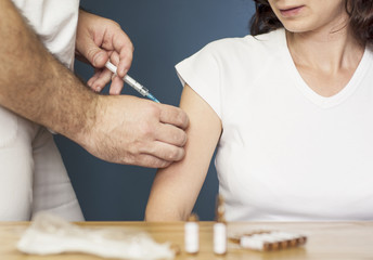 Doctor vaccinating a woman against flu