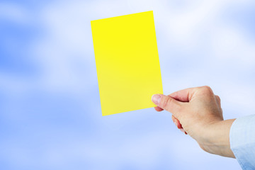 Hand shows a yellow card