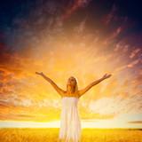 woman walking on wheat field over sunset