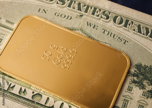 close-up of a 50g gold bar / ingot on a 20 Dollar note