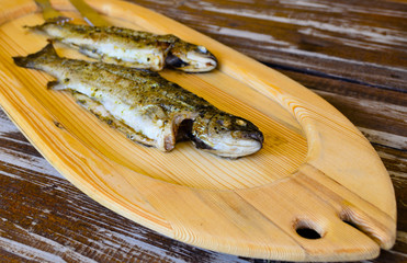 Two grilled fish resting on a wooden board
