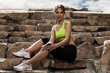 Beautiful young woman in fitwear relaxing