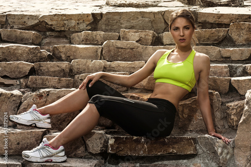 Beautiful young woman in fitwear relaxing
