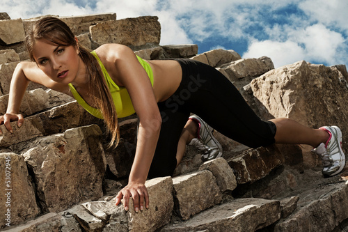Beautiful young woman in fitwear climbing