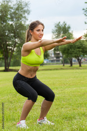 Beautiful young woman working out in a park