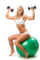 Smiling female lifting up a dumbbells seated on a fitness ball
