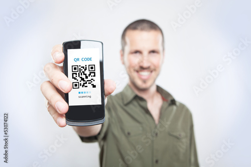 Youn man showing the phone with qr code
