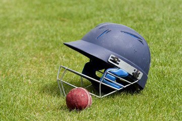 Cricket ball, bat and helmet on green grass of cricket pitch