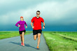 Couple running on country road, man and woman runners