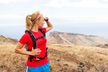 Young woman runner on trail in mountains