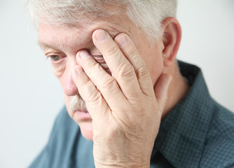 tired man rubbing his eye