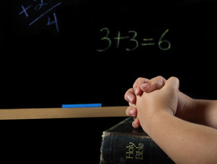 child's hand in prayer in school