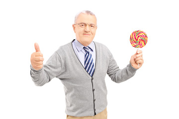 Smiling gentleman holding a colorful lollipop and giving thumb u