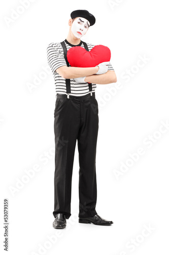 Full length portrait of a sad mime artist holding a red heart