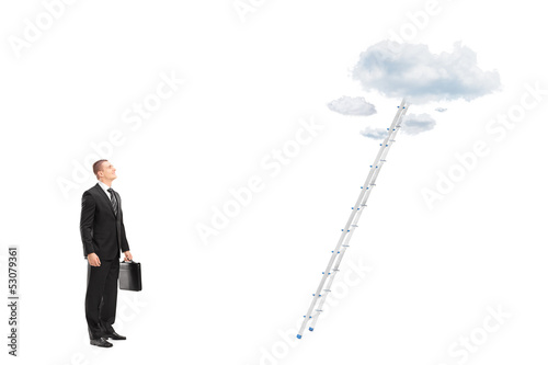 Businessman standing in front of a ladder with clouds looking up