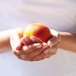Сочный, бархатистый персик в нежных руках