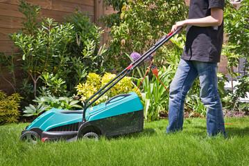 Jeune garçon tondant une pelouse