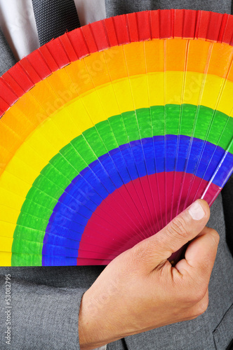 man in suit with a rainbow hand fan