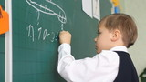 schoolboy writing on blackboard in classroom