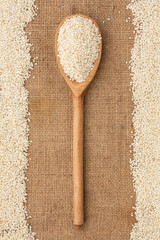 Wooden spoon with sesame seeds lying on sackcloth