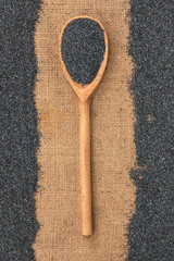Wooden spoon with poppy seeds lying on sackcloth