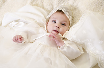 Little baby with ceremonial baptism clothes
