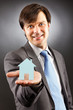 Young business man holding a model of a house on his palm