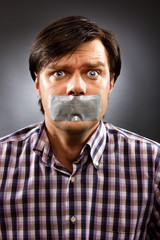 Young man with duct tape over his mouth