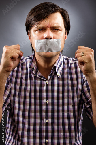Angry  young man with duct tape over his mouth
