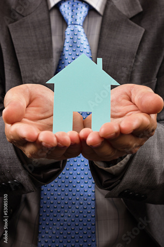 Business man holding a model of a house in his hands