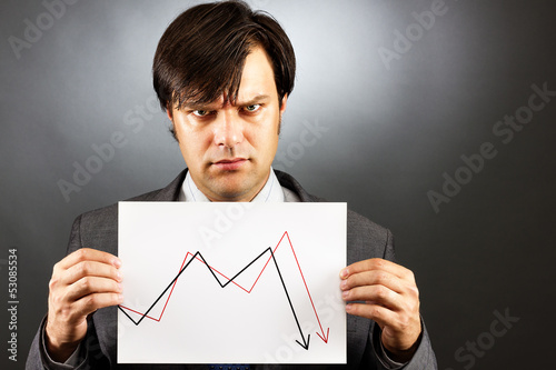 Angry businessman showing a falling graph of stock market