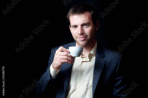 Low-key portrait of a business man drinking coffee