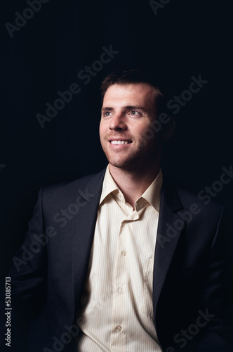 Low-key portrait of a smiling business man