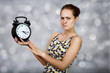 Angry girl with alarm clock at light background