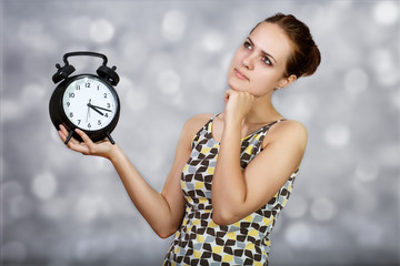 Thoughtful girl with alarm clocks at light background
