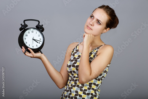 Thoughtful girl with alarm clocks at gray background