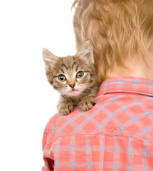 kitten peeping over the shoulder of a child. isolated on white