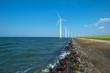Wind farm in a lake along a sunny dam