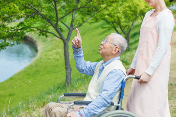 Asian senior man sitting on a wheelchair pointing