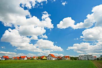 Blauer Himmel und Wolken über einer Siedlung