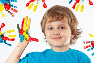 Young boy with painted hands on a background of hand prints