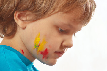 Portrait of a boy with painted face on a white background