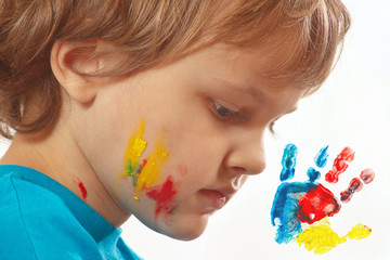 Portrait of a boy with painted face on background of handprint