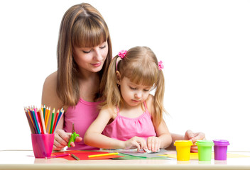 Mother and kid girl draw and cut together