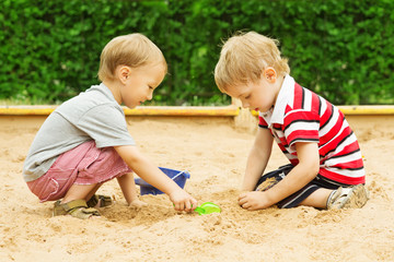 Two kids friends playing with sand outdoor. Summer season