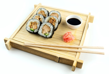 Teriyaki chicken sushi on bamboo tray with soy sauce and ginger