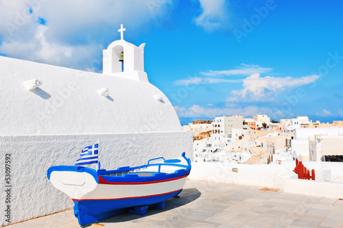 Traditional whitewashed chapel and small boat in Oia