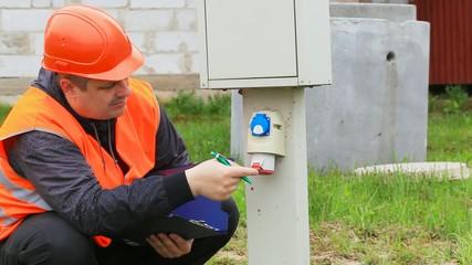Electrician with folder near switchboard