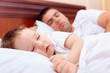 father and baby sleep in bed